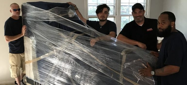 movers holding a piano