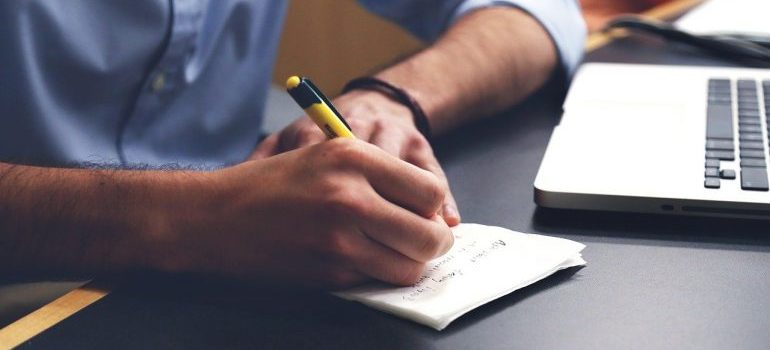 A person writing in the notebook.