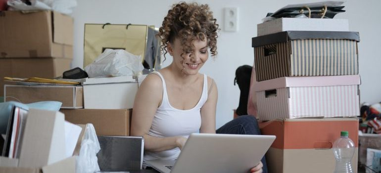 woman sitting on a floor with a laptop surrounded by boxes, waiting for long distance movers DC