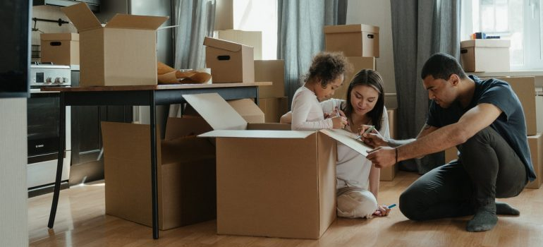 Woman, man and baby girl packing and waiting for local movers DC
