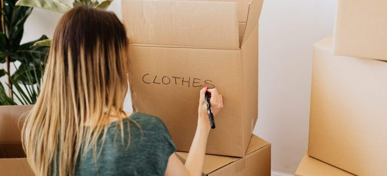 """woman writing """"clothes"""" on a cardboard moving box"""