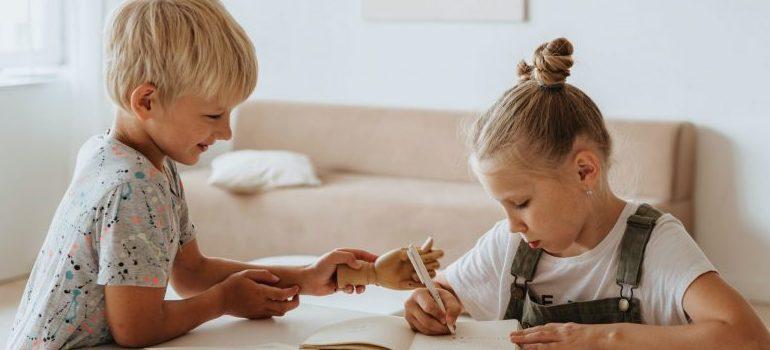 two kids studying, girl writing