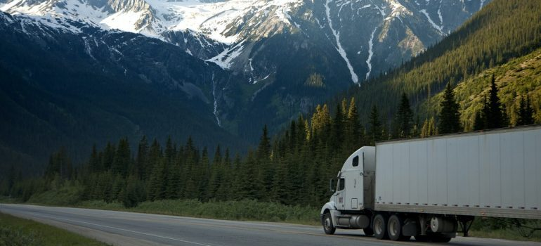 A white moving truck with mountains in the background.