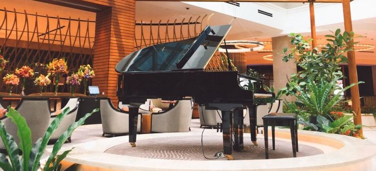 A piano in a well lit room waiting for piano moving