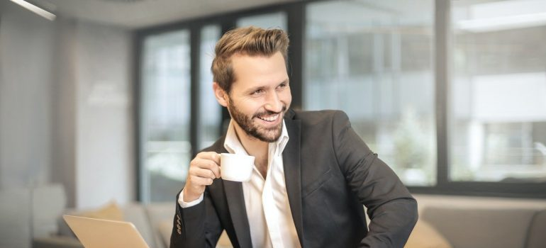 A smiling businessman holding white teacup.