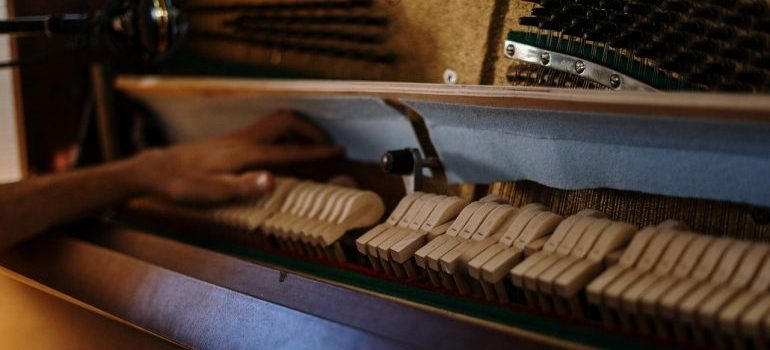 A hand touching the piano's internal sound mechanism