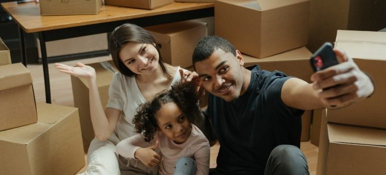 A happy family taking a selfie among moving boxes while waiting for local movers MD
