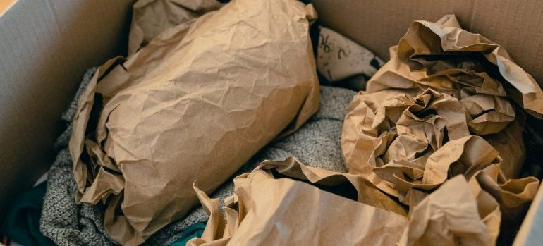 A cardboard box with clothes and crumpled paper.