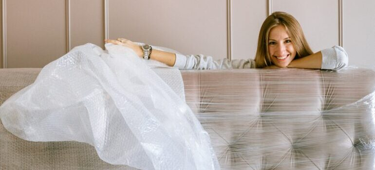 A woman unpacking a couch covered in wrapping.