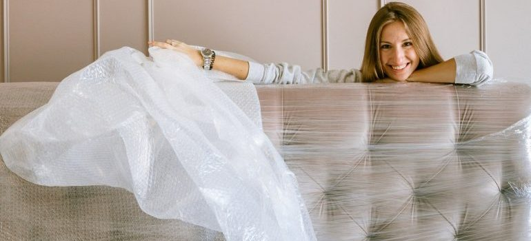 woman unwrapping her couch after furniture movers washington dc relocate it