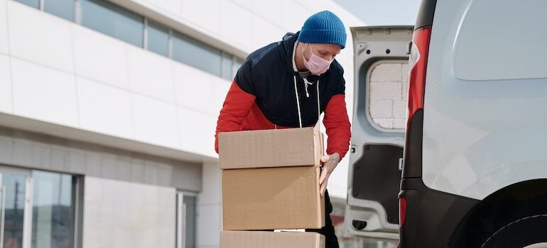 A man in a red and black hoodie loading boxes into a van.