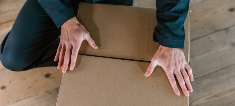 A person holding brown cardboard box
