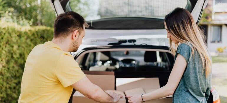 A man and a woman putting boxes in a car before hiring movers Bethesda MD has.