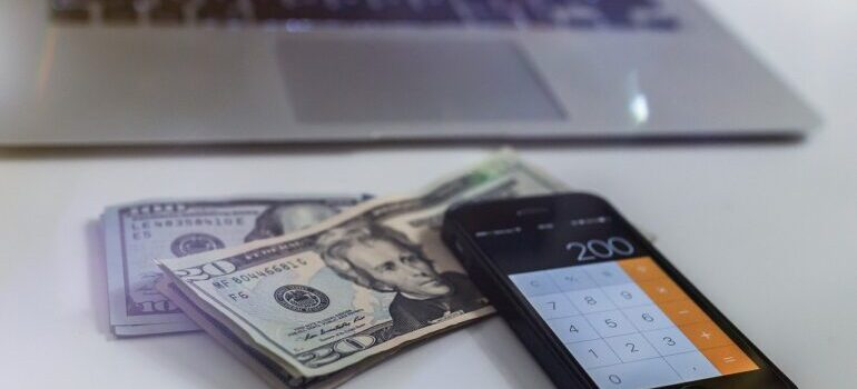 Dollar bills next to a phone and a laptop.