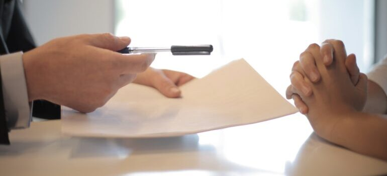 A business man give a contract to another man to sign