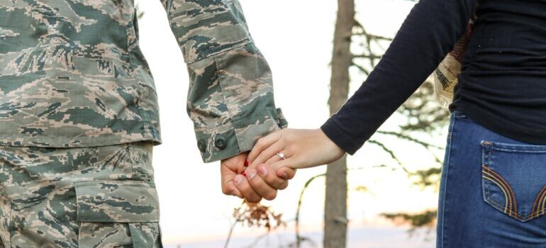 A solder and woman holding hands waiting for military movers