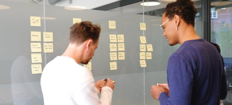 two men going through plans on a board