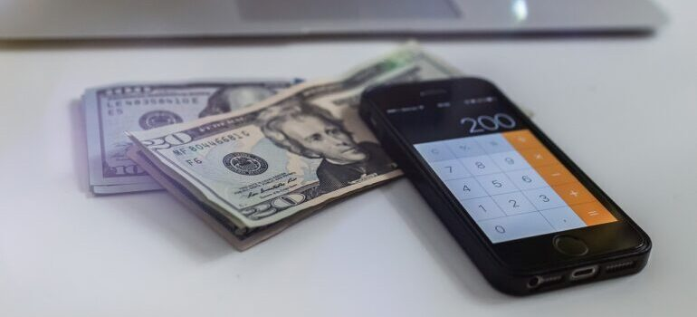 Dollar bills underneath a phone.