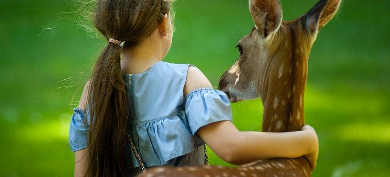 Little girl hugging a deer