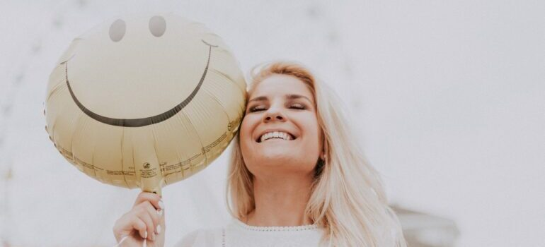 Woman smiling and holding a smiley baloon