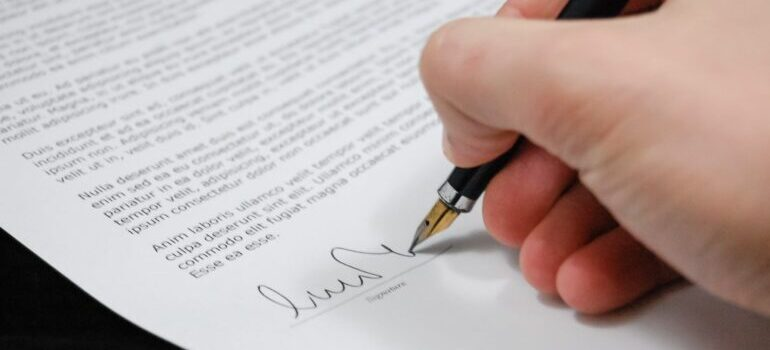 Person holding pen and signing the contract