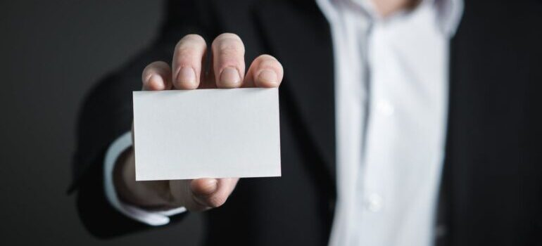 Man showing a card as symbol that you should ask your DC movers before your local move to show you license number