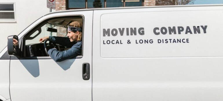 """a man in the drivers seat of a white van that says """"moving company"""""""