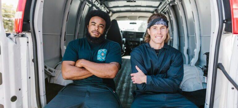 Men sitting in the back of a van.