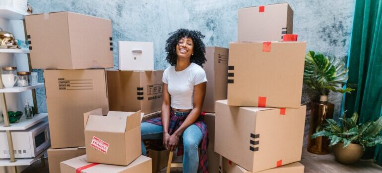 Woman sitting between many moving boxes