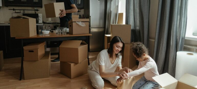 a mother packing items on the floor with her child while the father carries boxes in the background as a way to include your kids in your MD move