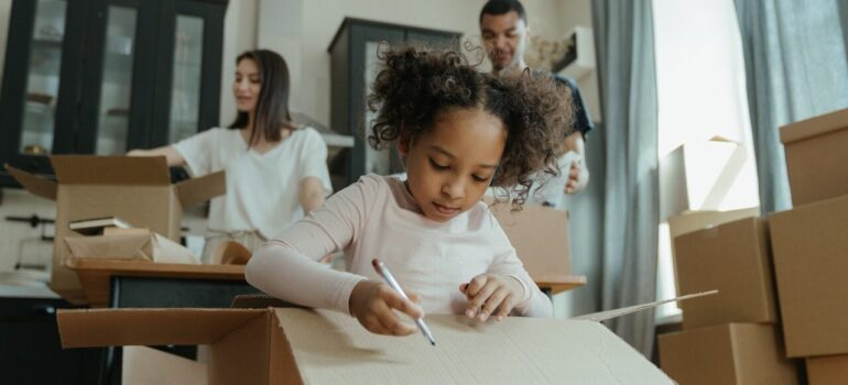 a small girl drawing on a cardboard box while her parents pack in the background