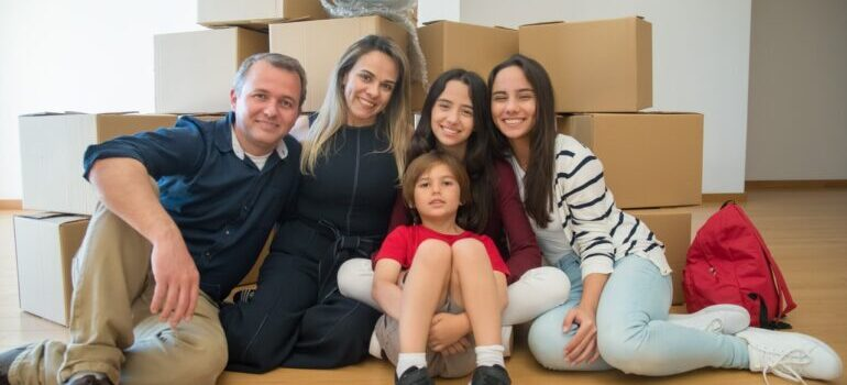 Family sitting in front of the moving boxes