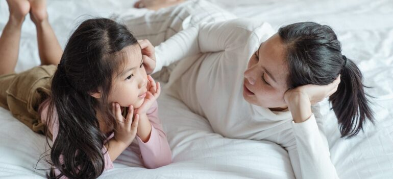 a mother talking to her daughter on the bed