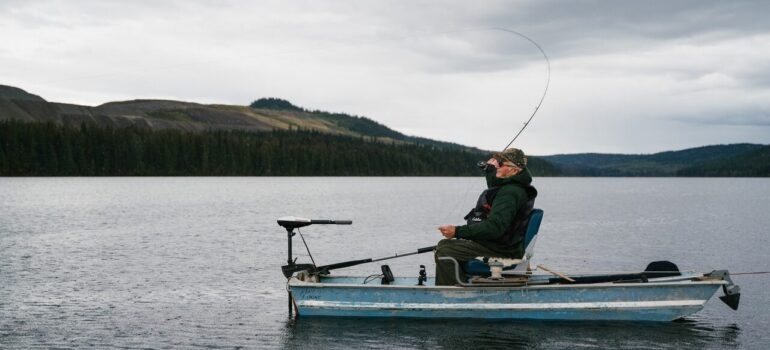 a person sitting in a boat in a lake while fishing