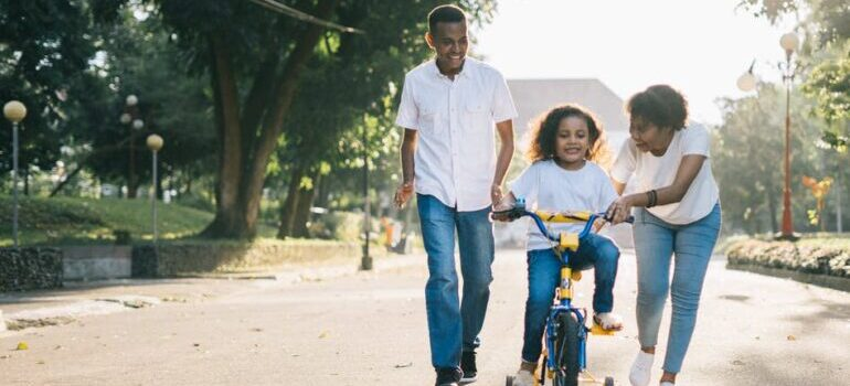 Parents teaching a child how to ride bicycle