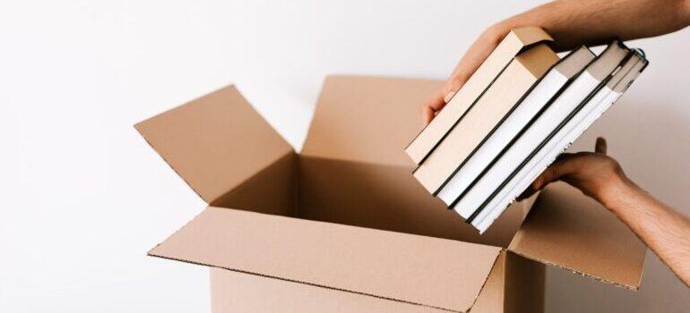 A person placing books into the box