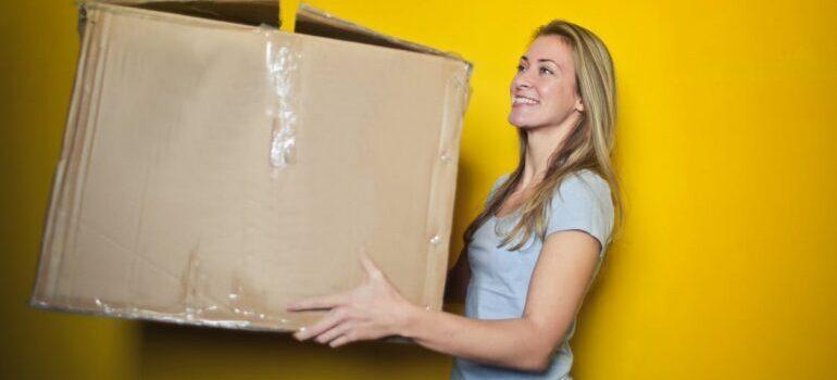 Women holding cardboard moving box