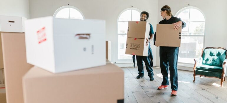 two men woking for a moving company carrying boxes through a home after their client was able to find reliable local movers in Maryland