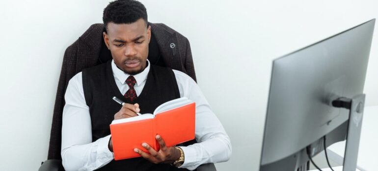 a man in a suit takes notes in front of his PC