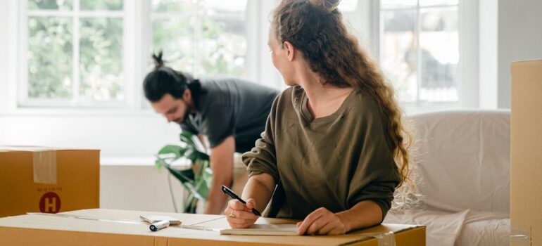 a man carrying a plant while the woman makes a list of items