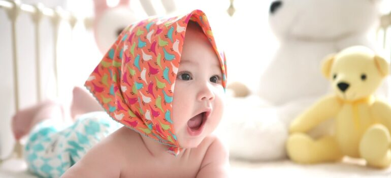 a baby toddler yawning in its crib with toys after you prepare your Alexandria home for a baby