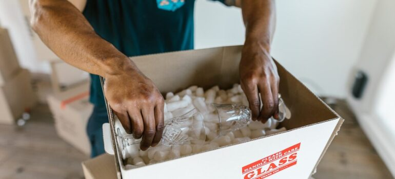 a mover carefully placing glasses inside a box with packing peanuts