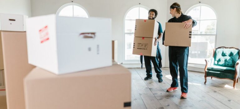 two moving company personnel carrying boxes in a home as a way for you to choose moving services you need the most when moving in Washington